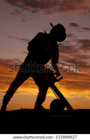 A silhouette of a cowboy using his saw to cut a log. - stock photo