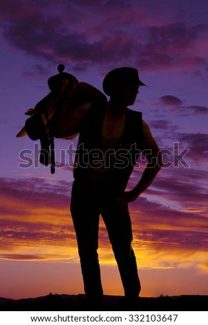 a silhouette of a cowboy with a saddle on his shoulder looking to the side. - stock photo