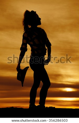 A silhouette of a cowgirl holding on to her hat looking up. - stock photo