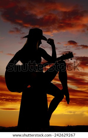 A silhouette of a cowgirl wearing her hat and playing her guitar. - stock photo