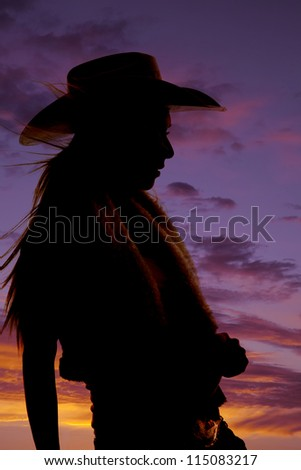 A silhouette of a cowgirl with a beautiful sunset behind her. - stock photo
