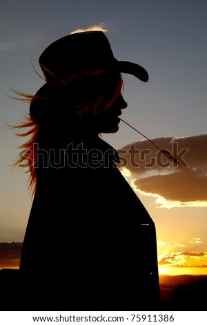 A silhouette of a cowgirl with wheat in her mouth with a beautiful sunset in the background. - stock photo