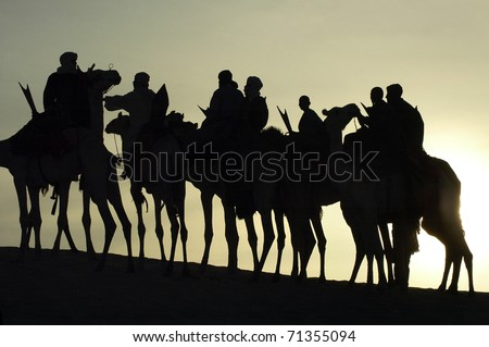 A silhouette of a group of Tuareg on their camels in the desert - stock photo