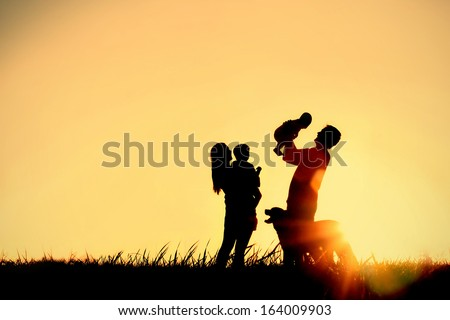 A silhouette of a happy family of four people, mother, father, baby, and child, and their dog in front of a sunsetting sky, with room for copy space or text - stock photo