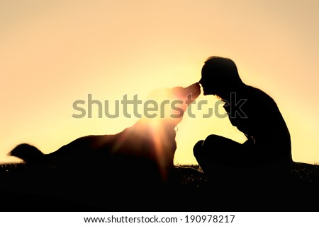 a silhouette of a happy young woman is sitting outside at sunset lovingly kissing her large German Shepherd mix breed dog. - stock photo