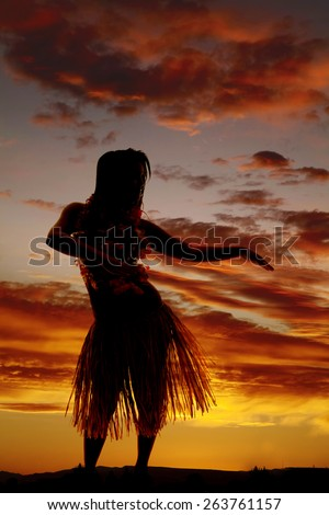 a silhouette of a Hawaiian woman dancing in the outdoors. - stock photo