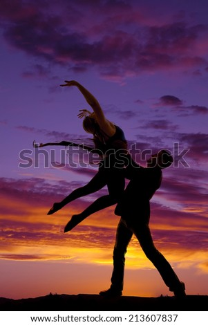 A silhouette of a man and woman dancing, he is doing a lift. - stock photo