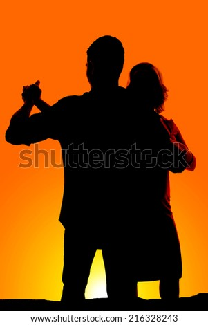 A silhouette of a man and woman dancing in the yellow sunset. - stock photo