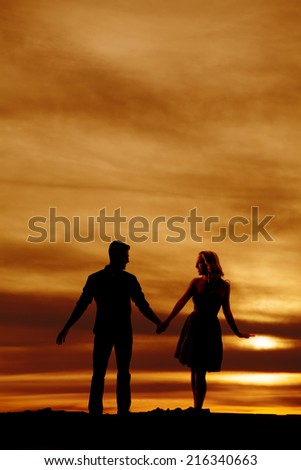 a silhouette of a man and woman holding hands with each other, walking together. - stock photo