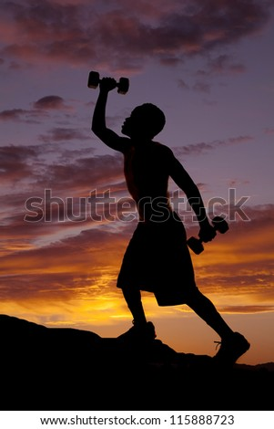 A silhouette of a man climbing up a hill working out with weights. - stock photo