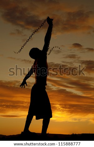 A silhouette of a man in the outdoors swinging a chain in the sky - stock photo