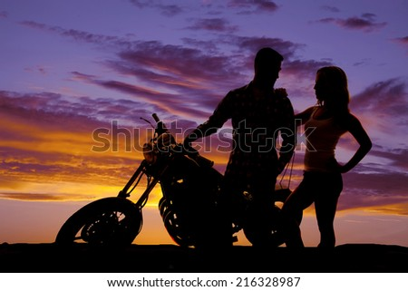 A silhouette of a man on his motorbike with his woman close by. - stock photo