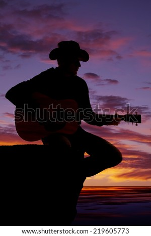 A silhouette of a man sitting on a rock ledge playing his guitar. - stock photo