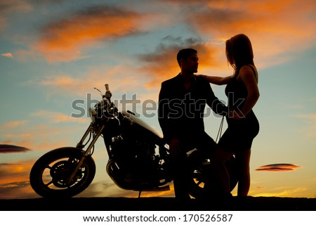 A silhouette of a man sitting on his bike holding on to his woman. - stock photo