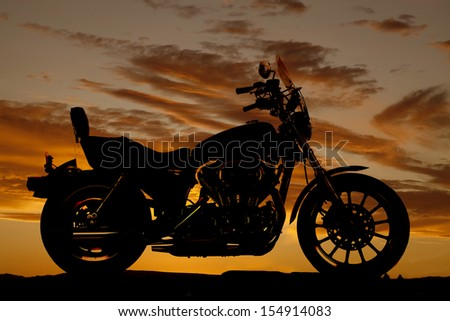 A silhouette of a motorcycle from a side view. - stock photo