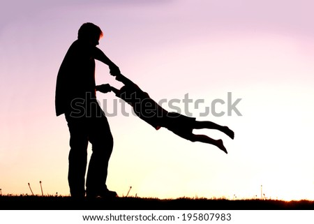 A silhouette of a playful young father spinning and dancing with his little child outside at sunset on a summer day. - stock photo