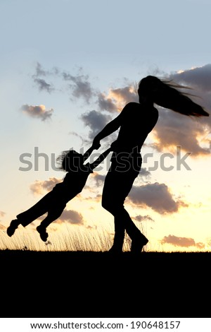 A silhouette of a playful young mother spinning and dancing with her little child outside at sunset. - stock photo