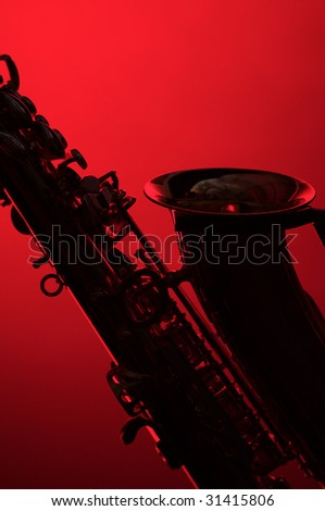 A silhouette of a saxophone close up isolated on a red background in the vertical format with copy space. - stock photo