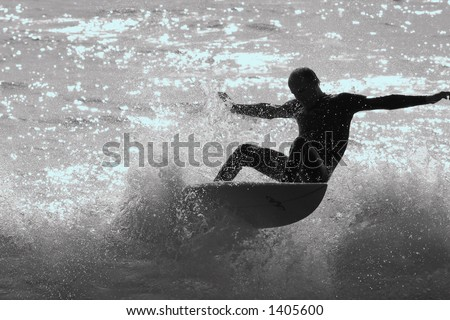 A silhouette of a surfer shredding the waves on the California coast. - stock photo