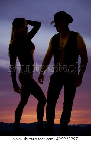 A silhouette of a woman and her cowboy standing close together. - stock photo