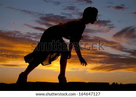 a silhouette of a woman bending over reaching for the ground. - stock photo