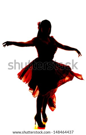 A silhouette of a woman dancing in her flowing dress. - stock photo