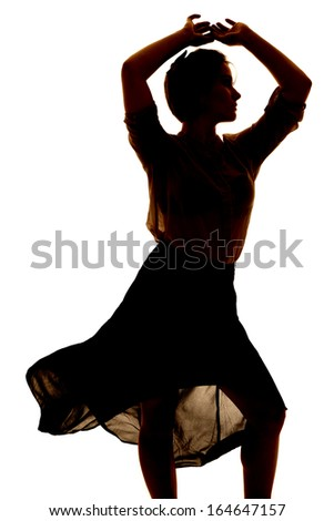 a silhouette of a woman dancing in her sheer dress. - stock photo