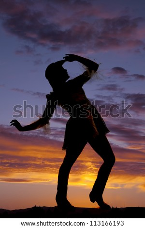 A silhouette of a woman dancing in the sunset. - stock photo