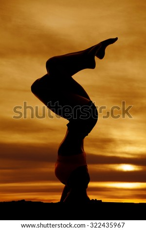 A silhouette of a woman doing a head stand in the outdoors. - stock photo