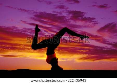 a silhouette of a woman doing a headstand in the outdoors. - stock photo