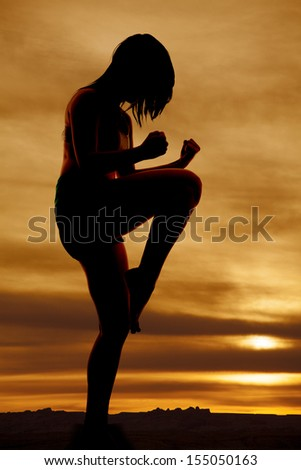 A silhouette of a woman doing a knee raise. - stock photo