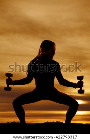 a silhouette of a woman doing a squat holding out her weights. - stock photo