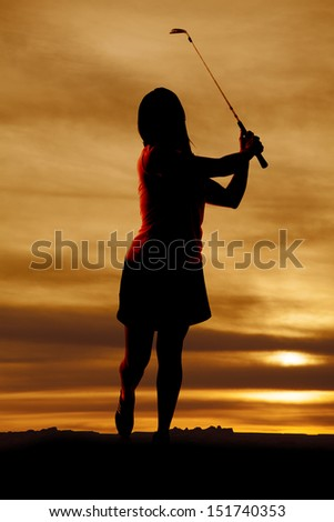 A silhouette of a woman golfing, with a beautiful sky behind her. - stock photo