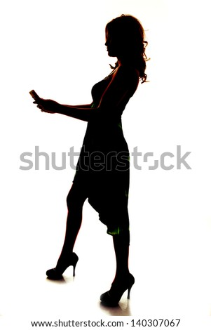 a silhouette of a woman holding on to her cell phone sending a text - stock photo