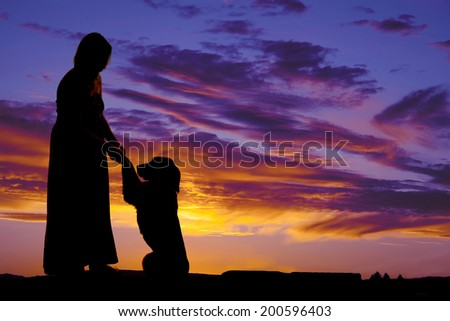 a silhouette of a woman holding on to her dogs paws - stock photo