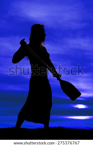 a silhouette of a woman  holding on to her paddle. - stock photo