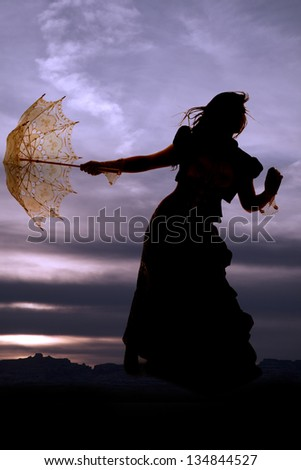 A silhouette of a woman holding on to her umbrella as the wind blows her hair. - stock photo