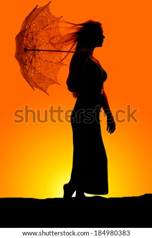 A silhouette of a woman holding on to her umbrella while the wind blows. - stock photo