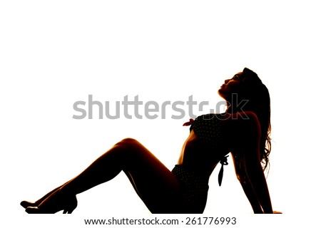 A silhouette of a woman in her bikini leaning back looking up. - stock photo