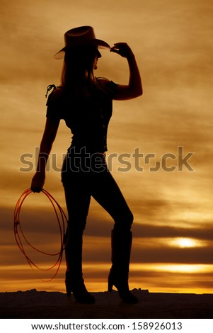 A silhouette of a woman in her cowgirl hat and holding on to a rope. - stock photo