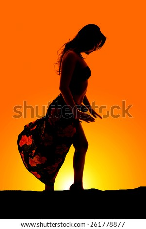 a silhouette of a woman in her sarong and bikini dancing in the outdoors. - stock photo