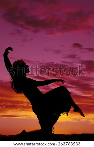 A silhouette of a woman in her sarong on the beach posing. - stock photo
