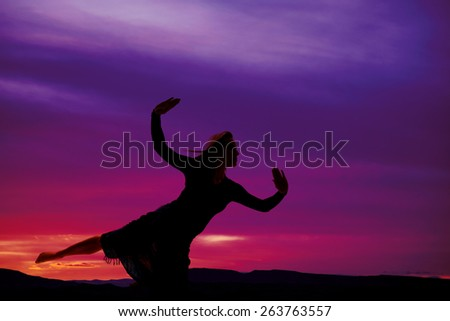 A silhouette of a woman in her sarong stretching and posing. - stock photo