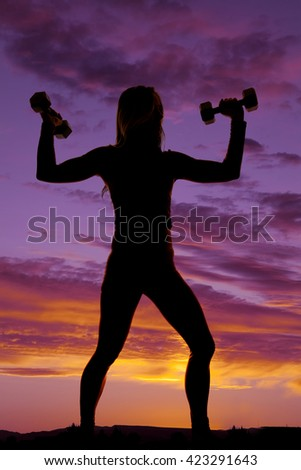 A silhouette of a woman in the outdoors working out with dumbbells. - stock photo