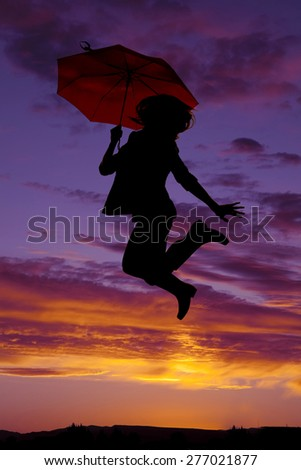 A silhouette of a woman jumping up in her rain boots, and holding an umbrella. - stock photo