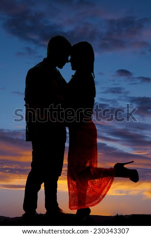 a silhouette of a woman kicking up her leg, as she cuddles with her man. - stock photo