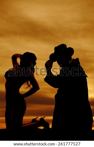 a silhouette of a woman kneeling with her cowboy behind her. - stock photo