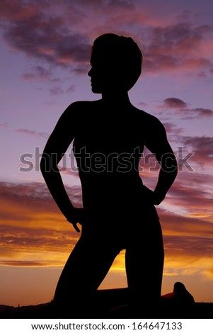 A silhouette of a woman kneeling with her hands on her hips. - stock photo