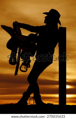 a silhouette of a woman leaning against a pole holding on to her horse saddle. - stock photo