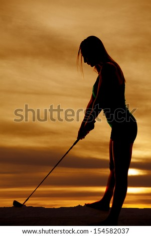 A silhouette of a woman looking down at her golf club. - stock photo